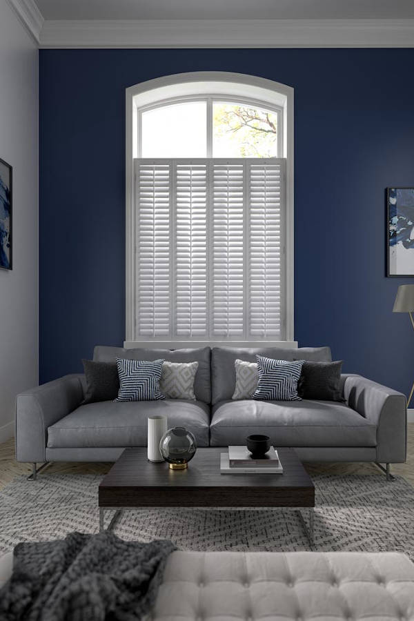 living room with sofa and large window with shutters