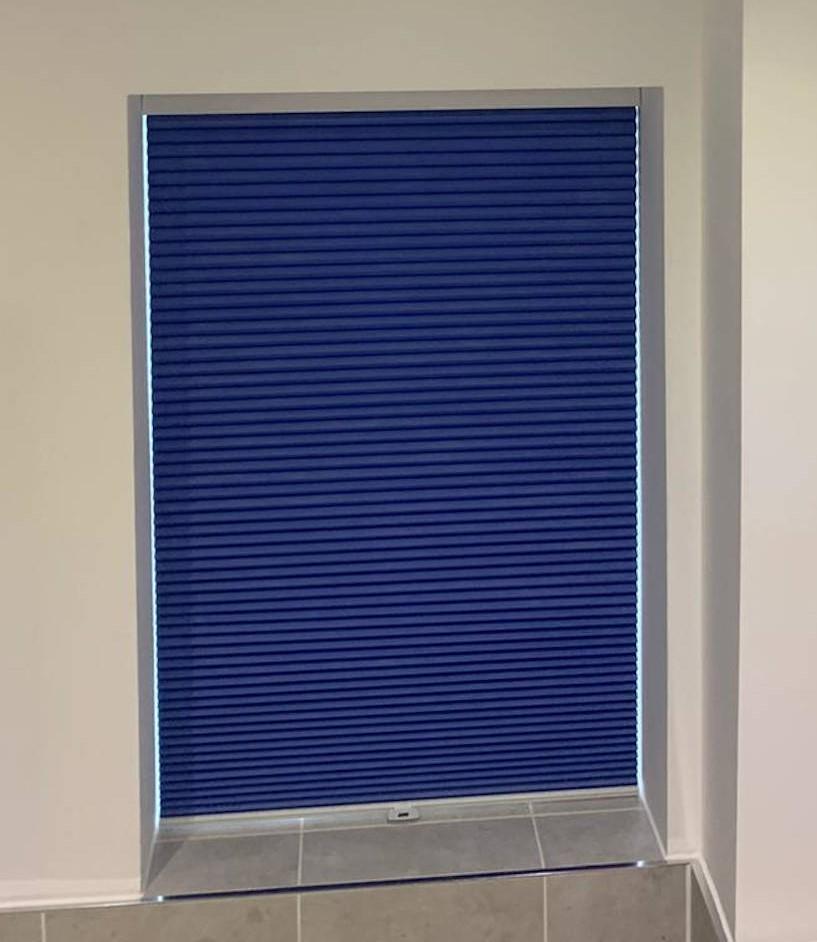 Bathroom window blind, coloured blue.