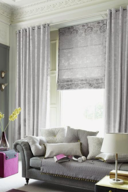 Living room in traditional house, with large window, dressed with a Roman Blind and curtains.